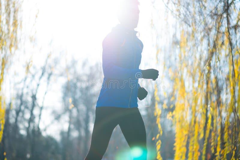 Νέος αθλητής που τρέχει στο πάρκο το κρύο ηλιόλουστο πρωί φθινοπώρου Υγιής έννοια τρόπου ζωής και αθλητισμού στοκ φωτογραφίες