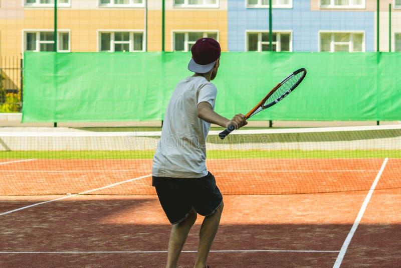 Νέος αθλητικός αρσενικός τενίστας στην πρακτική καλοκαιρινό εκπαιδευτικό κάμπινγκ στοκ εικόνα
