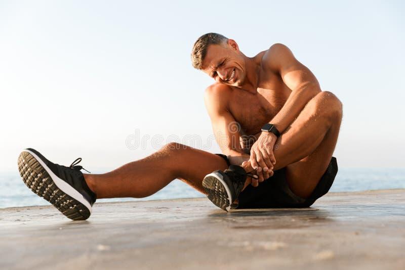 Νέος αθλητικός τύπος γυμνοστήθων που πάσχει από έναν πόνο αστραγάλων στοκ εικόνες