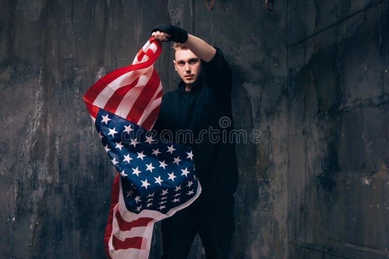Νέος ΑΜΕΡΙΚΑΝΙΚΟΣ πατριώτης με την πετώντας αμερικανική σημαία στοκ φωτογραφίες