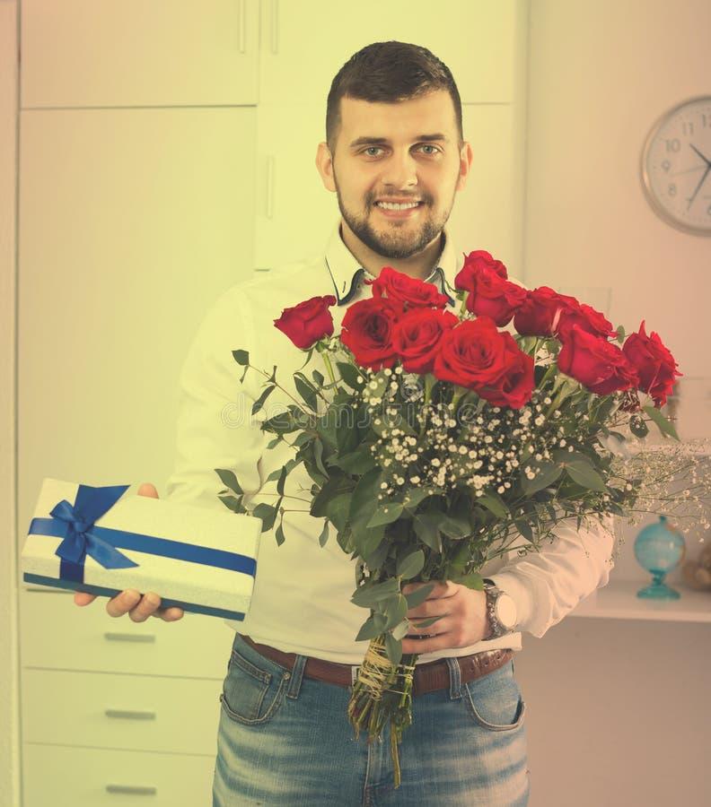 Νέος αρσενικός έτοιμος χαμόγελου με την ανθοδέσμη και το δώρο στοκ εικόνες