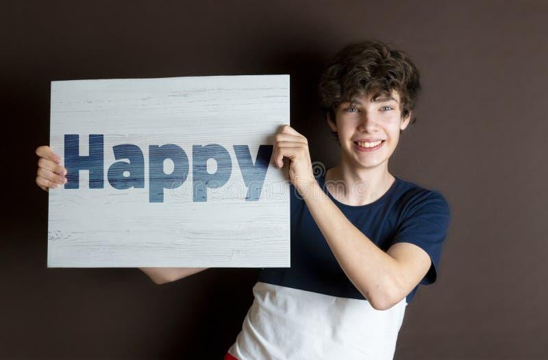 Νέος αρσενικός έφηβος που κρατά ένα ξύλινο πλαίσιο με το ευτυχές κείμενο λέξης, νέα φανταστική έννοια φ ζωής στοκ εικόνα με δικαίωμα ελεύθερης χρήσης