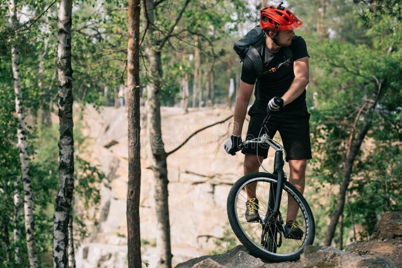 νέος αρσενικός ακραίος ποδηλάτης στο προστατευτικό κράνος που οδηγά στο ποδήλατο βουνών στοκ φωτογραφίες