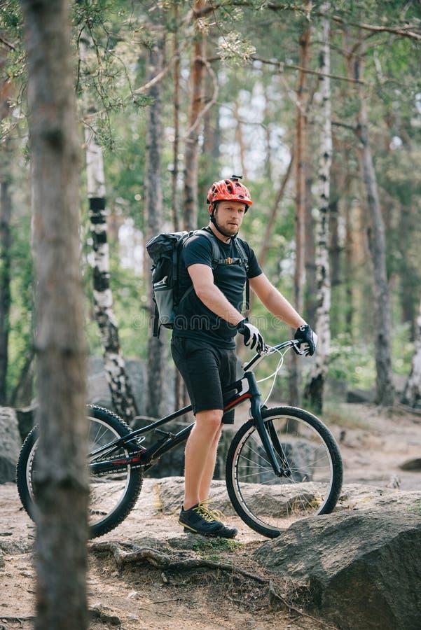 νέος αρσενικός ακραίος ποδηλάτης στο προστατευτικό κράνος που στέκεται με το ποδήλατο βουνών στοκ φωτογραφία με δικαίωμα ελεύθερης χρήσης