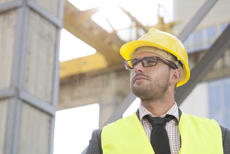 Νέος αρσενικός αρχιτέκτονας που φορά το σκληρό καπέλο που εξετάζει μακριά το εργοτάξιο οικοδομής στοκ φωτογραφία