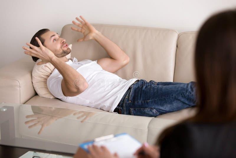 Νέος αρσενικός ασθενής που βρίσκεται στον καναπέ που μιλά στο θηλυκό ψυχολόγο στοκ εικόνες