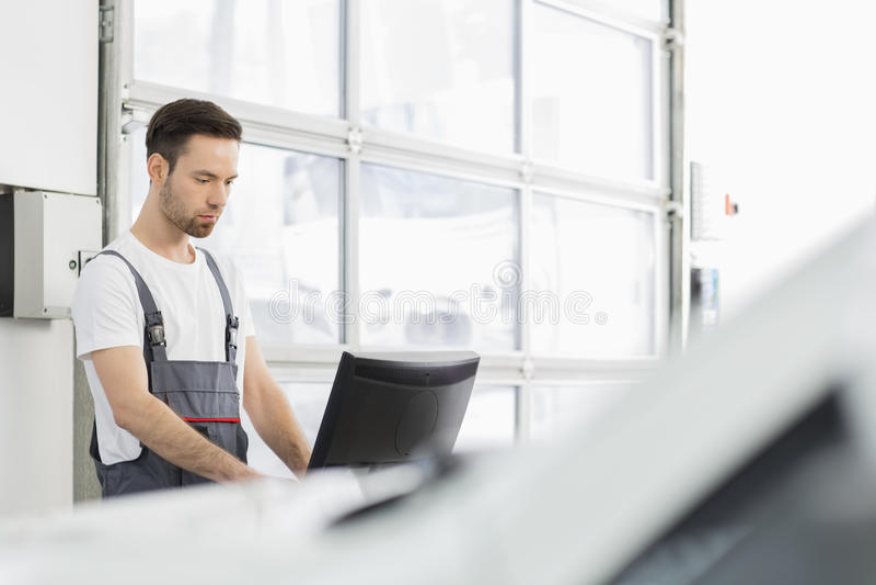 Νέος αρσενικός αυτοκινητικός μηχανικός χρησιμοποιώντας υπολογιστής στο κατάστημα επισκευής στοκ εικόνες