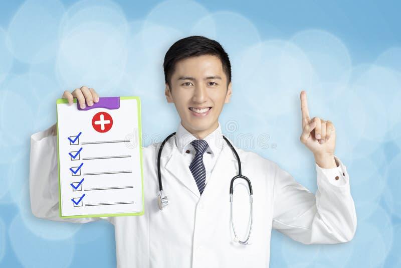Νέος αρσενικός γιατρός που παρουσιάζει ιατρική αναφορά στοκ φωτογραφία