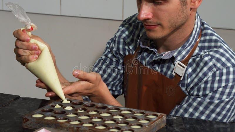 Νέος αρσενικός ζαχαροπλάστης που προσθέτει την πλήρωση βανίλιας στις φόρμες καραμελών σοκολάτας στοκ εικόνα