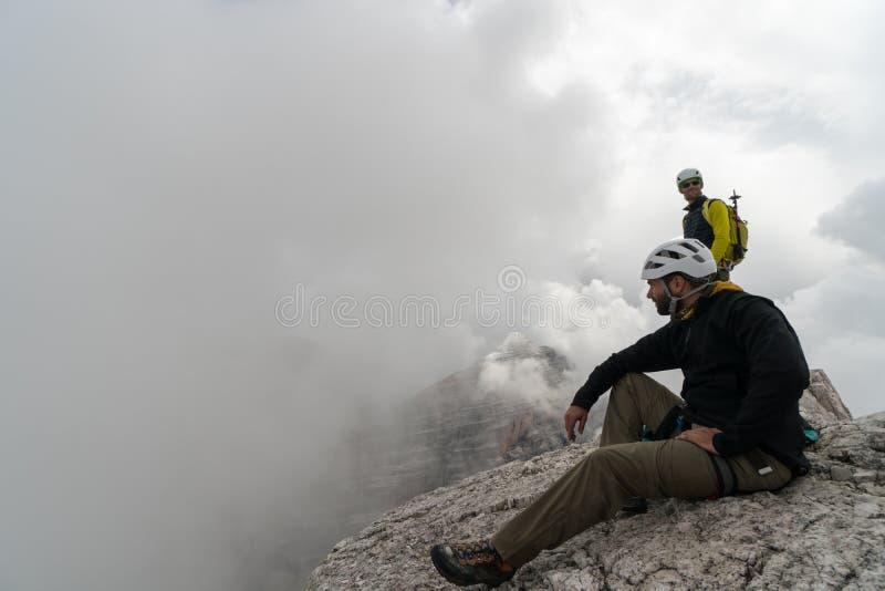 Νέος αρσενικός ορειβάτης βουνών σε μια αιχμή βουνών δολομίτη που απολαμβάνει τη θέα με τον οδηγό του που στέκεται πίσω στοκ εικόνες