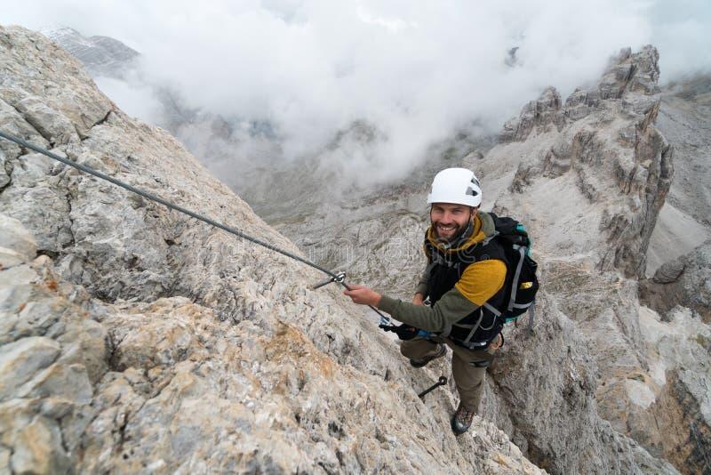 Νέος αρσενικός ορειβάτης σε ένα απότομο και εκτεθειμένο πρόσωπο βράχου που αναρριχείται στο α μέσω του όμορφου αρσενικού ορειβάτη στοκ φωτογραφία