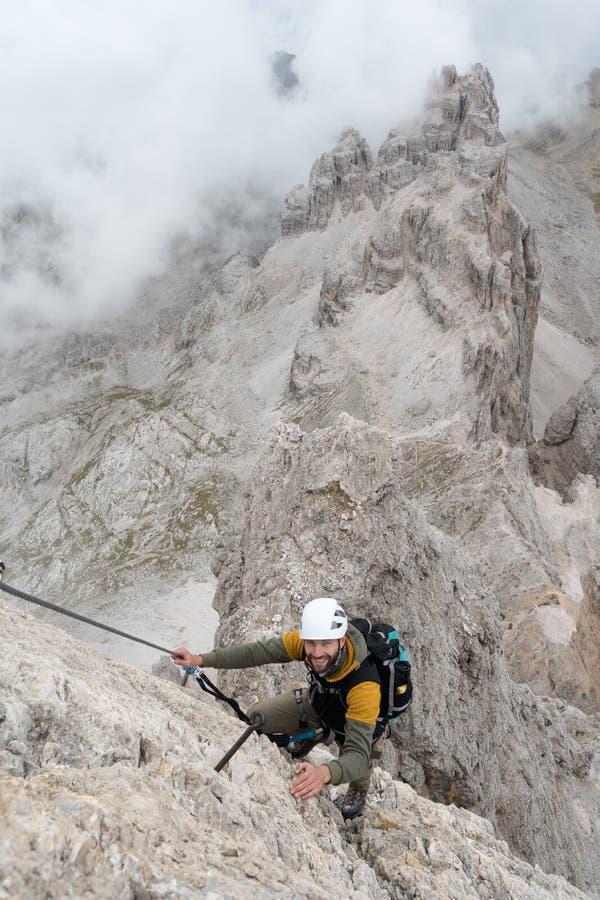 Νέος αρσενικός ορειβάτης σε ένα απότομο και εκτεθειμένο πρόσωπο βράχου που αναρριχείται στο α μέσω του όμορφου αρσενικού ορειβάτη στοκ εικόνα