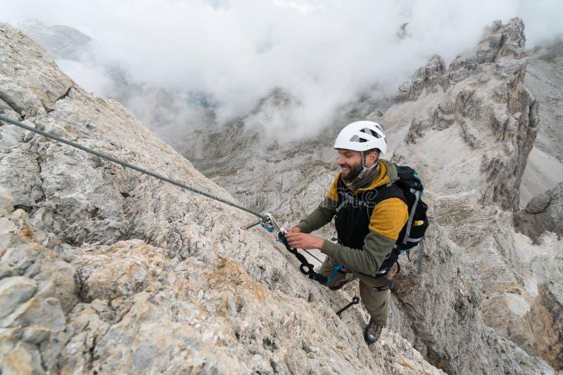 Νέος αρσενικός ορειβάτης σε ένα απότομο και εκτεθειμένο πρόσωπο βράχου που αναρριχείται στο α μέσω του όμορφου αρσενικού ορειβάτη στοκ εικόνες με δικαίωμα ελεύθερης χρήσης