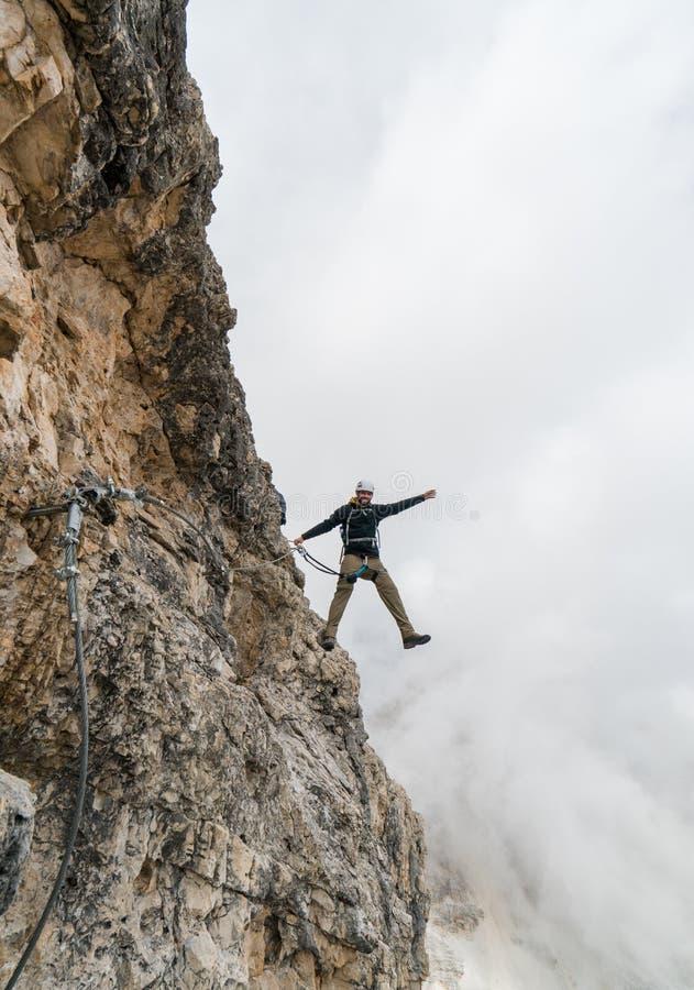 Νέος αρσενικός ορειβάτης σε ένα απότομο και εκτεθειμένο πρόσωπο βράχου που αναρριχείται στο α μέσω του όμορφου αρσενικού ορειβάτη στοκ φωτογραφίες με δικαίωμα ελεύθερης χρήσης