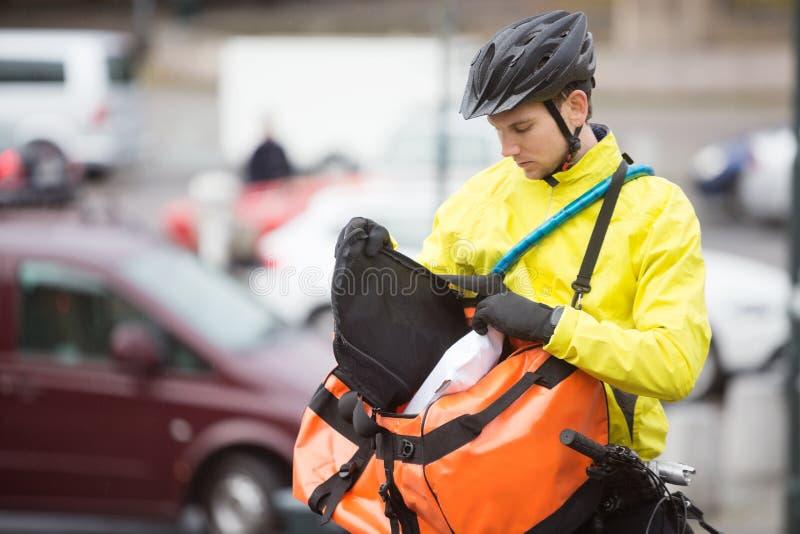 Νέος αρσενικός ποδηλάτης που βάζει τη συσκευασία στην τσάντα αγγελιαφόρων στοκ φωτογραφίες με δικαίωμα ελεύθερης χρήσης