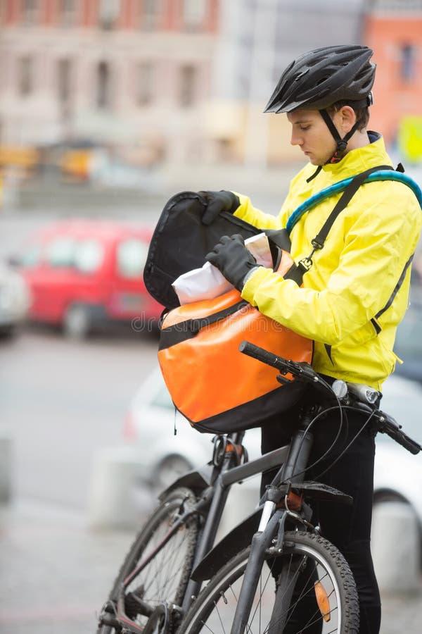 Νέος αρσενικός ποδηλάτης που βάζει τη συσκευασία στην τσάντα αγγελιαφόρων στοκ φωτογραφία