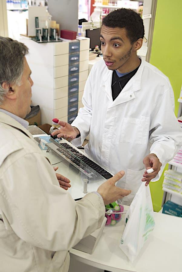Νέος αρσενικός φαρμακοποιός μιγάδων που μιλά με έναν πελάτη στοκ φωτογραφία