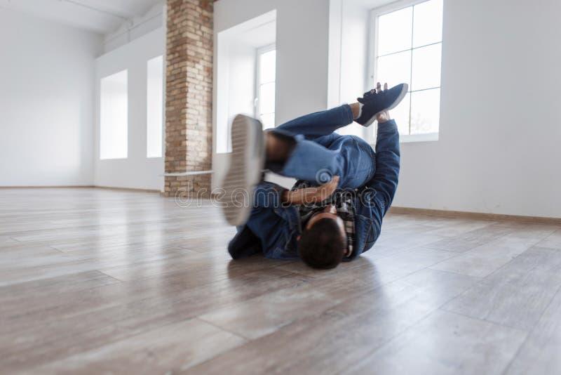 Νέος αρσενικός χορευτής στο μοντέρνο φόρεμα τζιν που χορεύει στο στούντιο στοκ εικόνες