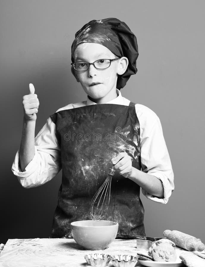 Νέος αρχιμάγειρας μαγείρων αγοριών χαριτωμένος σε ομοιόμορφο και καπέλο στο λεκιασμένο αλεύρι προσώπου με τα γυαλιά που στέκονται στοκ εικόνα
