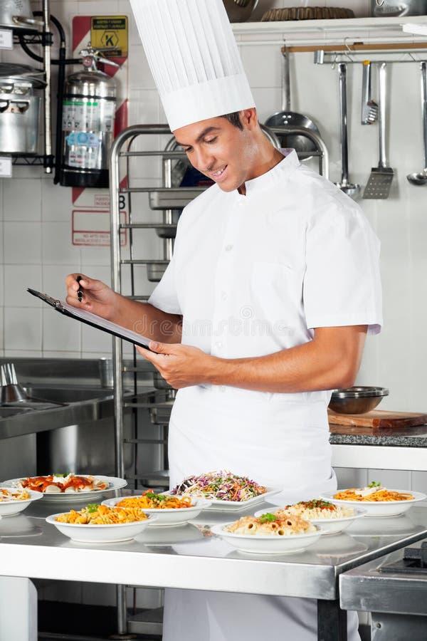 Νέος αρχιμάγειρας με την περιοχή αποκομμάτων στην κουζίνα στοκ εικόνα