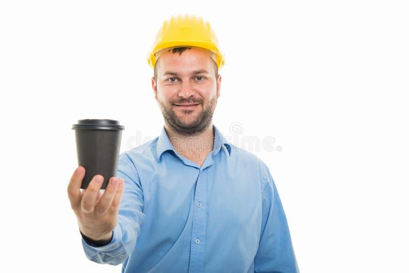 Νέος αρχιτέκτονας με την κίτρινη εκμετάλλευση κρανών για να πάει φλυτζάνι καφέ στοκ εικόνες