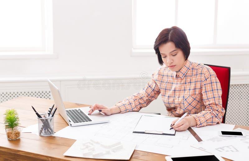 Νέος αρχιτέκτονας που εργάζεται με τα σχεδιαγράμματα στο γραφείο στοκ εικόνες με δικαίωμα ελεύθερης χρήσης