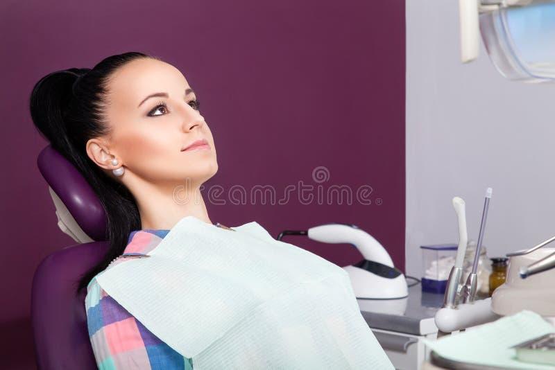Νέος ασθενής γυναικών που περιμένει τον οδοντίατρο έτοιμο για την εξέταση στοκ εικόνες