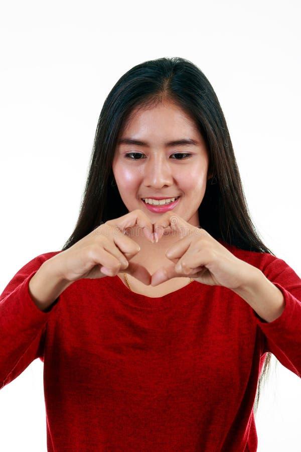 Νέος ασιατικός έφηβος που κάνει τη μορφή συμβόλων καρδιών από τα χέρια της στο άσπρο υπόβαθρο στοκ φωτογραφίες