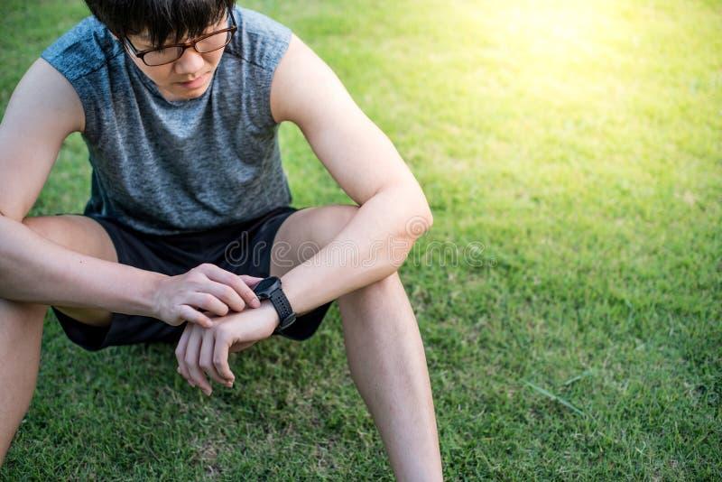 Νέος ασιατικός δρομέας ατόμων που εξετάζει το έξυπνο ρολόι μετά από να τρέξει στοκ εικόνες