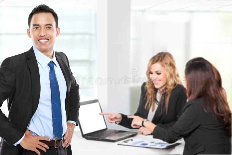 Νέος ασιατικός επιχειρηματίας, με την ομάδα του πίσω Απομονωμένος στο λευκό στοκ εικόνες με δικαίωμα ελεύθερης χρήσης