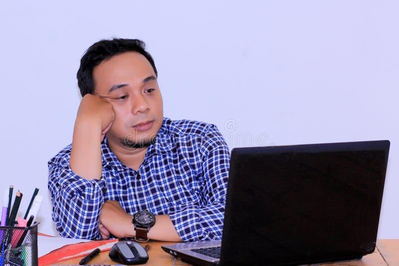 Νέος ασιατικός επιχειρηματίας που εξετάζει την οθόνη lap-top στοκ εικόνες