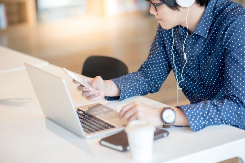 Νέος ασιατικός επιχειρηματίας που χρησιμοποιεί το smartphone που λειτουργεί με το lap-top στοκ εικόνες