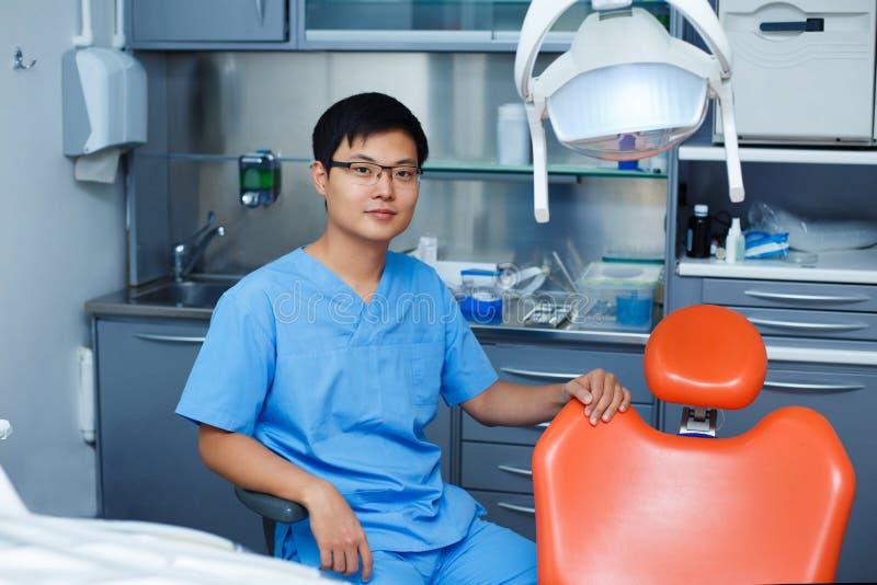 Νέος ασιατικός οδοντίατρος ατόμων με την καρέκλα οδοντιάτρων στην κλινική Dentis στοκ εικόνα