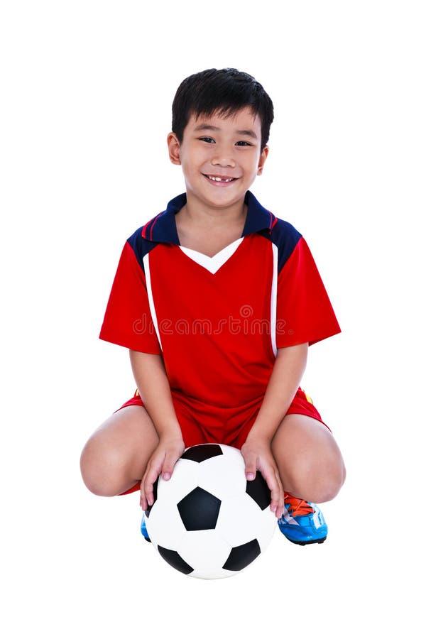 Νέος ασιατικός ποδοσφαιριστής με το ποδόσφαιρο που χαμογελά και που κρατά socc στοκ φωτογραφία με δικαίωμα ελεύθερης χρήσης
