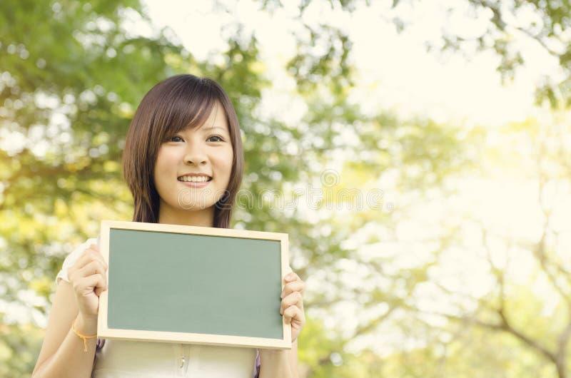 Νέος ασιατικός σπουδαστής κοριτσιών κολλεγίων που κρατά τον κενό πίνακα κιμωλίας στοκ φωτογραφία