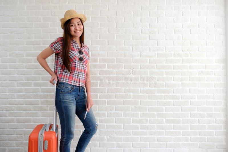 Νέος ασιατικός ταξιδιώτης γυναικών που κρατά το έξυπνες τηλέφωνο και τις αποσκευές στο άσπρο δωμάτιο με το διάστημα αντιγράφων, δ στοκ φωτογραφίες με δικαίωμα ελεύθερης χρήσης