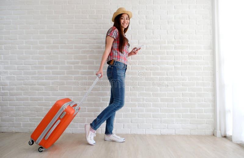 Νέος ασιατικός ταξιδιώτης γυναικών που κρατά το έξυπνες τηλέφωνο και τις αποσκευές στο άσπρο δωμάτιο με το διάστημα αντιγράφων, δ στοκ φωτογραφία