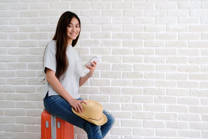 Νέος ασιατικός ταξιδιώτης γυναικών που κρατά το έξυπνο τηλέφωνο, χαμογελώντας και sitt στοκ εικόνες με δικαίωμα ελεύθερης χρήσης