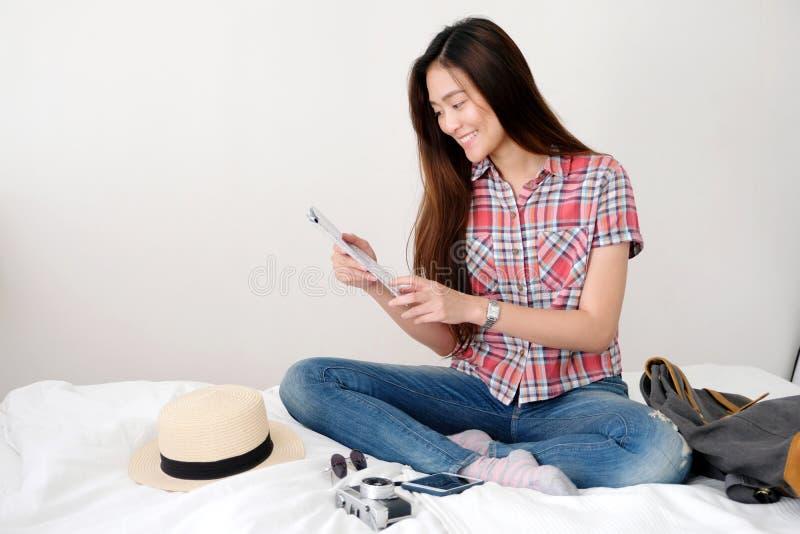 Νέος ασιατικός χάρτης ταξιδιωτικής εκμετάλλευσης γυναικών καθμένος στο κρεβάτι με το καπέλο, τη κάμερα, eyeglasses, την τσάντα κα στοκ φωτογραφίες