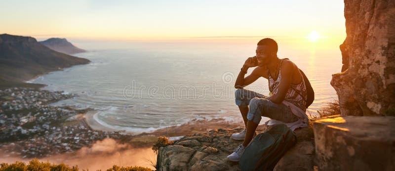 Νέος αφρικανικός έφηβος που μιλά σε ένα κινητό τηλέφωνο πεζοπορία στοκ εικόνα