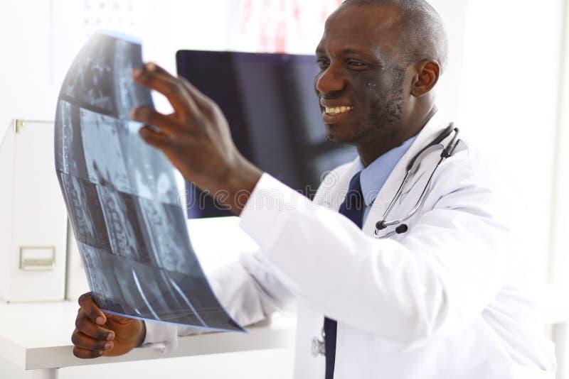 Νέος αφρικανικός ιατρός πορτρέτου που κρατά την υπομονετική ακτίνα X ` s στοκ εικόνες με δικαίωμα ελεύθερης χρήσης