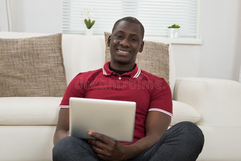 Νέος Αφρικανός που χρησιμοποιεί την ψηφιακή ταμπλέτα στοκ φωτογραφίες