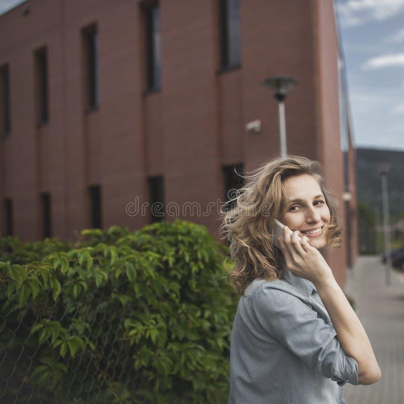 Νέος, βέβαιος, επιχειρησιακή γυναίκα στη βιασύνη, που μιλά στο smartphone στοκ εικόνα με δικαίωμα ελεύθερης χρήσης