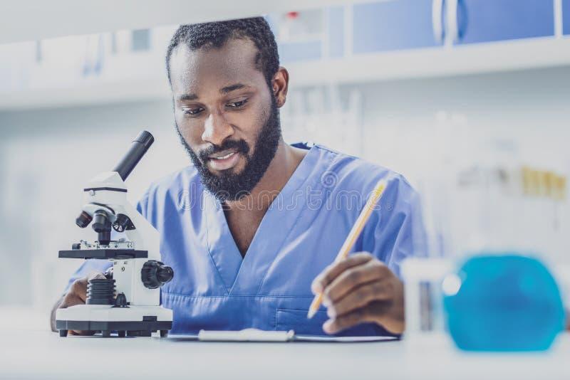 Νέος βιολόγος στην μπλε ομοιόμορφη έκθεση γραψίματος στοκ φωτογραφία