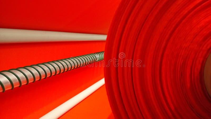 Νέος βιομηχανικός κόκκινος ρόλος, κόκκινο υπόβαθρο Έννοια: υλικό, ύφασμα, κατασκευή, εργοστάσιο ενδυμάτων, νέα δείγματα των υφασμ στοκ εικόνες