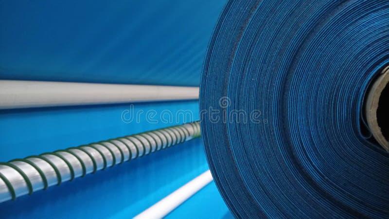 Νέος βιομηχανικός μπλε ρόλος, μπλε υπόβαθρο Έννοια: υλικό, ύφασμα, κατασκευή, εργοστάσιο ενδυμάτων, νέα δείγματα των υφασμάτων στοκ εικόνες