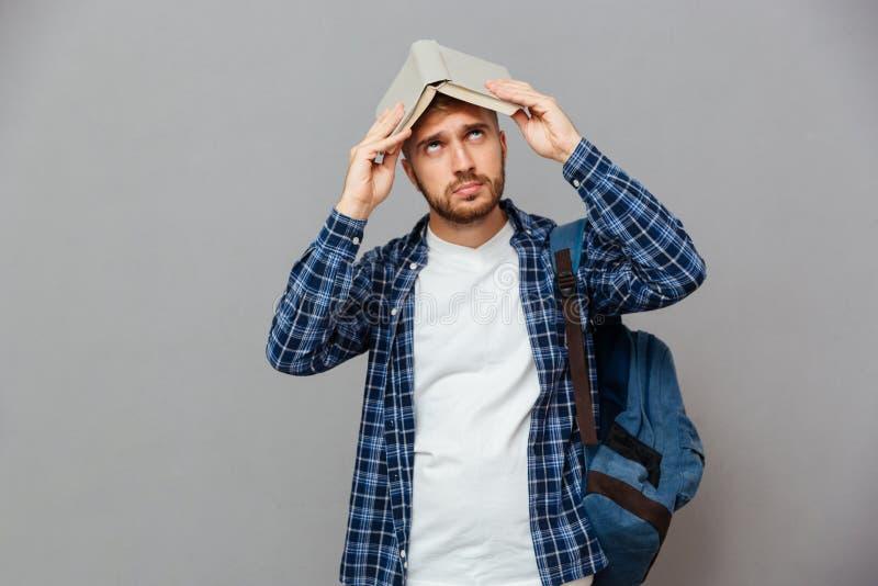 Νέος γενειοφόρος άνδρας σπουδαστής με το ανοικτό βιβλίο στο κεφάλι του στοκ εικόνες με δικαίωμα ελεύθερης χρήσης