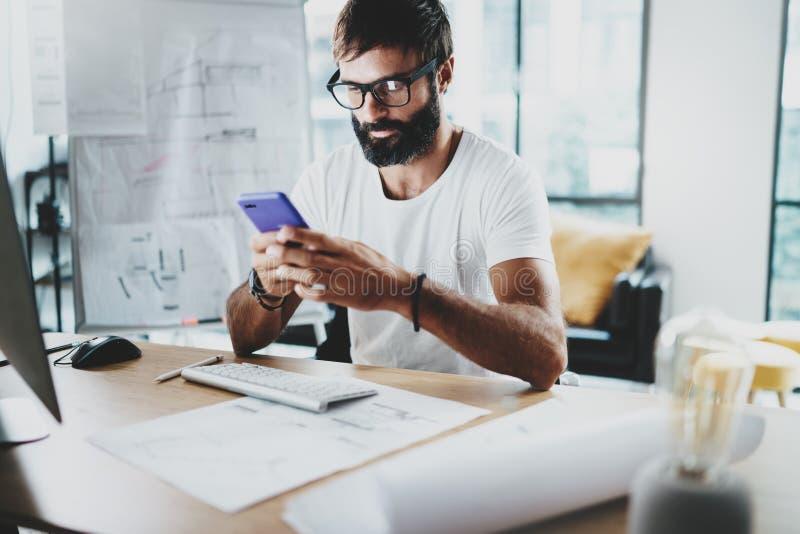 Νέος γενειοφόρος γραφικός σχεδιαστής που φορά τα γυαλιά ματιών και που εργάζεται στο σύγχρονο στούντιο-γραφείο σοφιτών χρησιμοποί στοκ εικόνα με δικαίωμα ελεύθερης χρήσης
