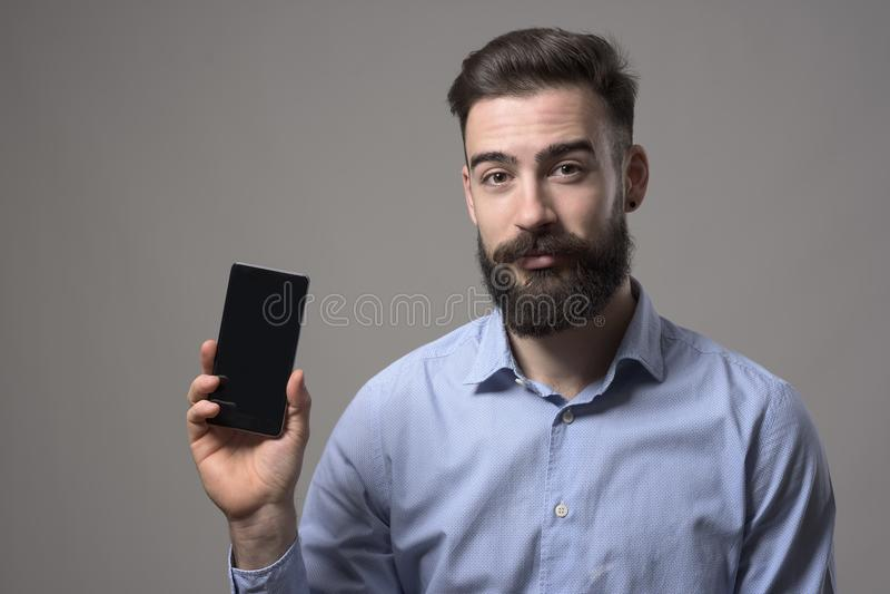 Νέος γενειοφόρος επιχειρηματίας ή προγραμματιστής που παρουσιάζει κενή έξυπνη τηλεφωνική οθόνη για τη διαφήμιση στοκ εικόνα