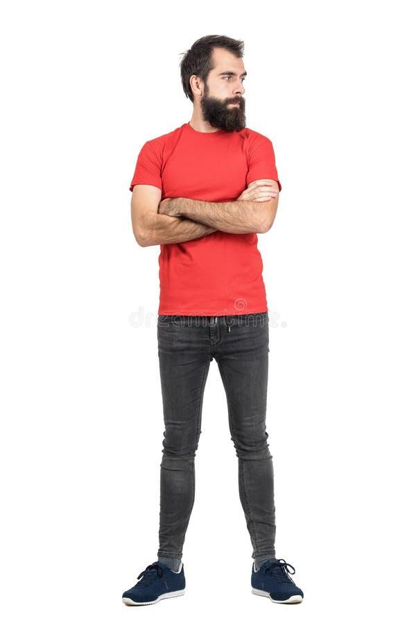 Νέος γενειοφόρος τύπος στην κόκκινη μπλούζα με τα διασχισμένα όπλα που κοιτάζουν μακριά στοκ φωτογραφίες με δικαίωμα ελεύθερης χρήσης